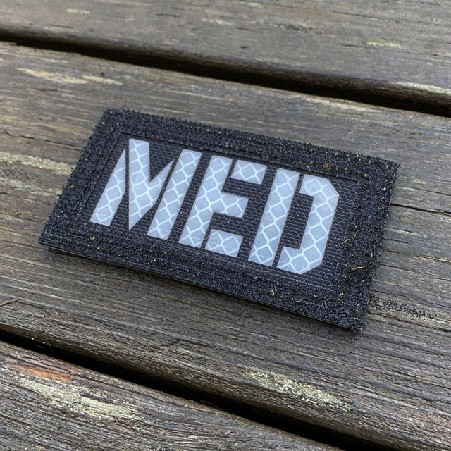 White text on a IR - MED Black-Green Reversible Glow Hook Patch
