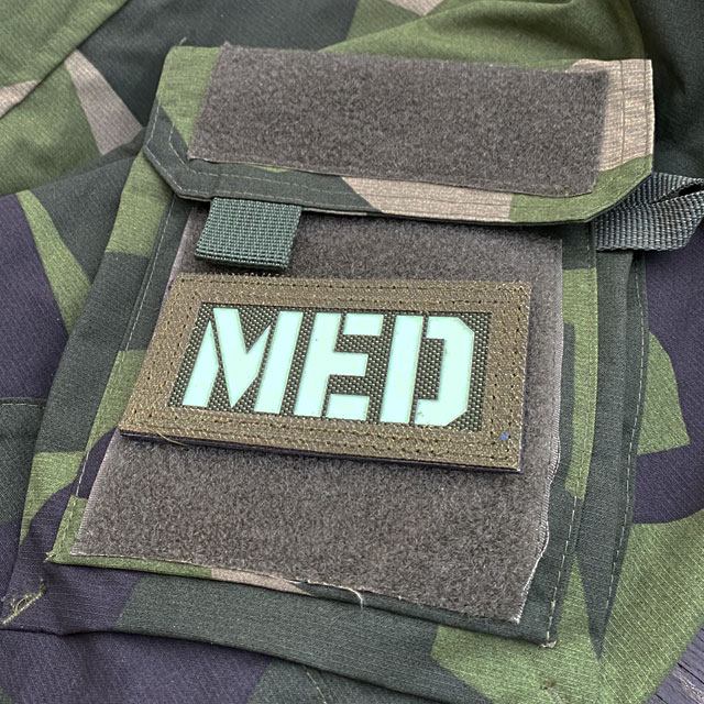A IR - MED Black-Green Reversible Glow Hook Patch mounted on a M90 sleeve green side out seen from the side