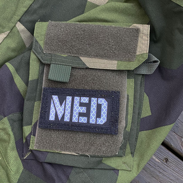 A IR - MED Black-Green Reversible Glow Hook Patch mounted on a M90 sleeve black side out