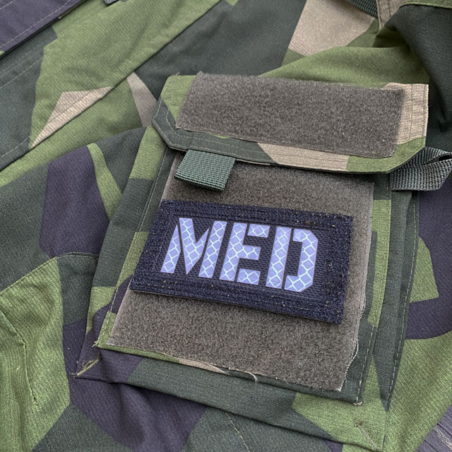 A IR - MED Black-Green Reversible Glow Hook Patch mounted on a M90 sleeve black side out seen from the side