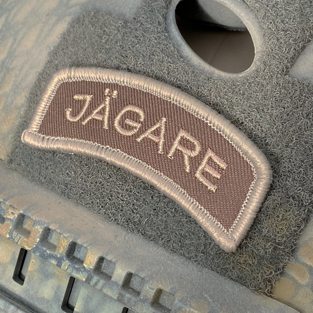 Seen slightly from the side a JÄGARE Desert Hook Patch mounted with hook and loop on a helmet