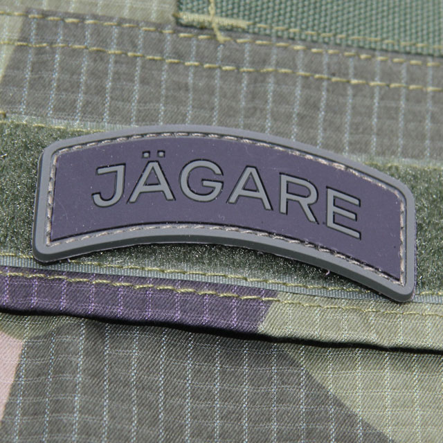 A JÄGARE Green/Black/Green PVC Patch with M90 camouflage background.