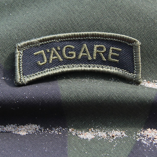 M90 camouflage background and a JÄGARE Patch Green/Black/Green M14.