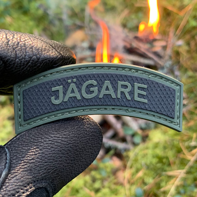 JÄGARE Green/Black PVC Patch M15 at the camp site in the Swedish forest.
