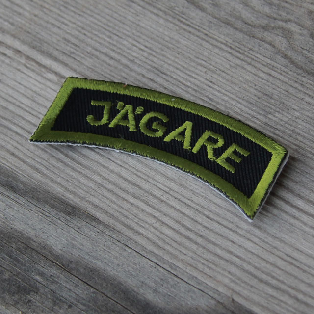 A JÄGARE Patch Jungle Green on a wooded background.