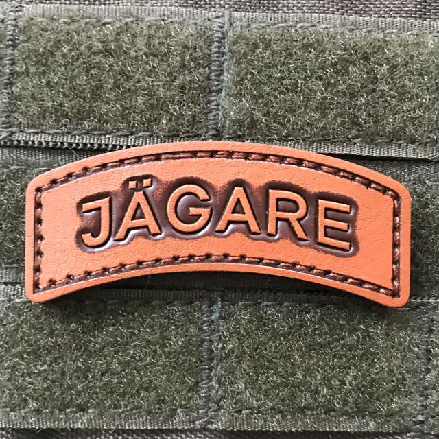 A bright and shiny JÄGARE Leather Hook Patch on green background.