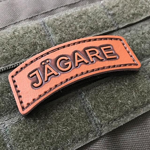 A JÄGARE Leather Hook Patch on green velcro background.