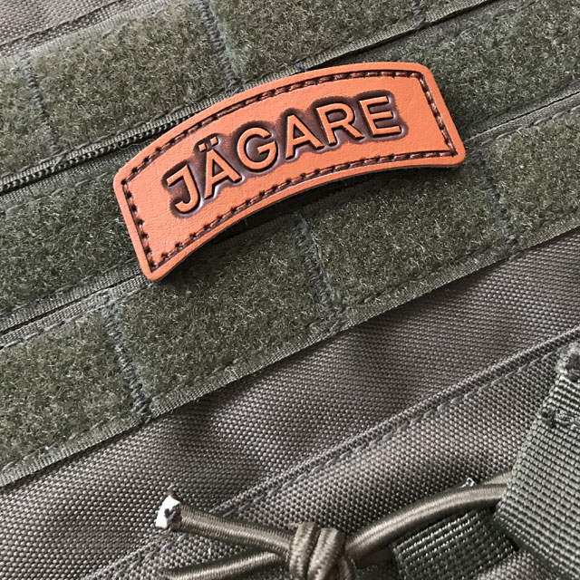 The JÄGARE Leather Hook Patch Tab mounted on a ranger green plate carrier.