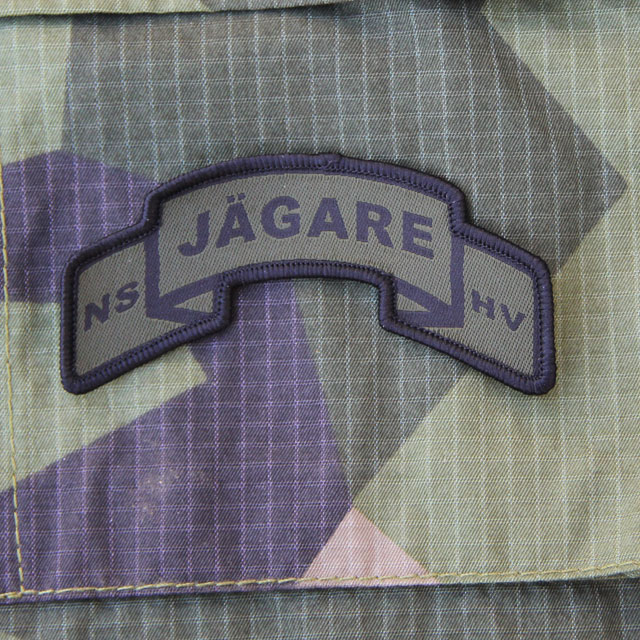 A JÄGARE Scroll Patch on a M90 Camouflage background.
