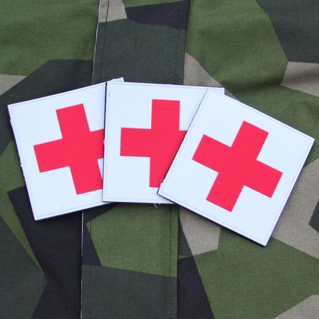 The Medic Cross PVC Hook Patch x 3 Bundle with M90 camouflage background.