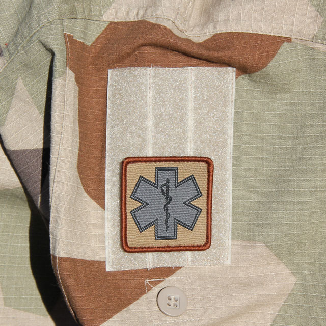 Mounted MEDIC Desert Star Hook Patch on the arm of a M90K Desert camouflage jacket.
