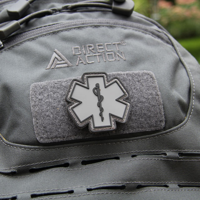 A MEDIC PVC Star Black Grey Hook Patch mounted on a rucksack.