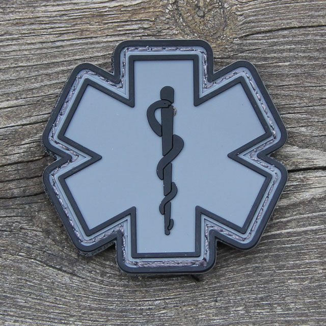 Wood background and a MEDIC PVC Star Black Grey Hook Patch.