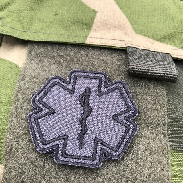 A mounted MEDIC Star of Life Black Grey Hook Patch on a armpocket of a M90 Camouflage jacket.
