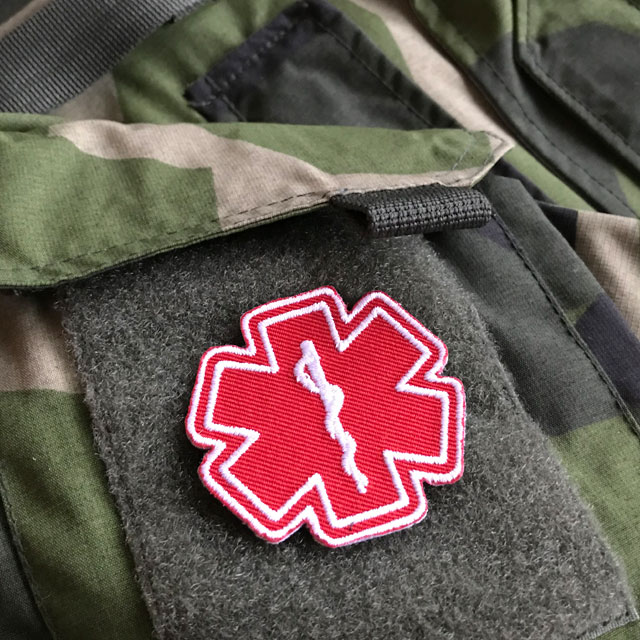 M90 camouflage jacket and a MEDIC Star of Life Red White Hook Patch.