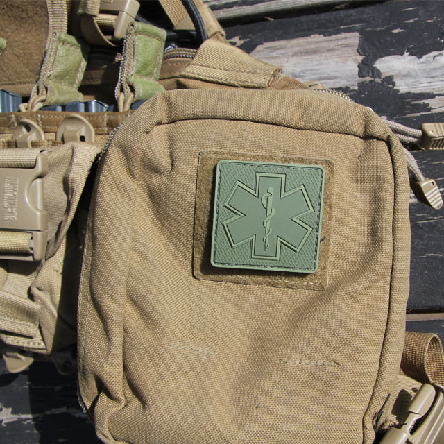 A MEDIC Subdued Green Star Hook PVC Patch mounted on a desert colored pouch.