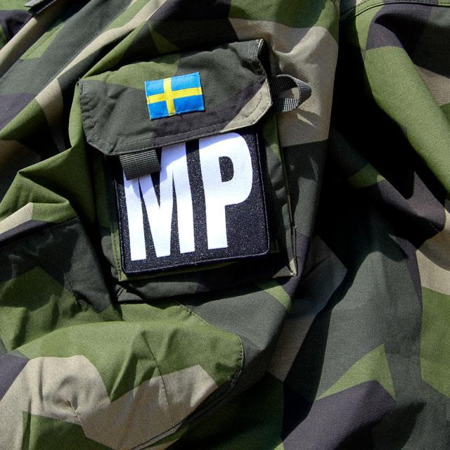 En Militärpolis Large Patch monterad på en M90 kamouflage jacka.