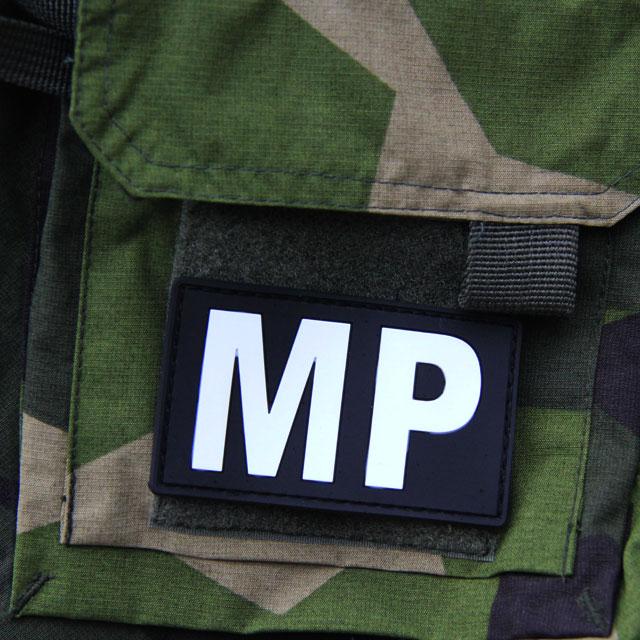 En Militärpolis PVC Patch monterad på ärmen på en M90 kamouflage jacka.