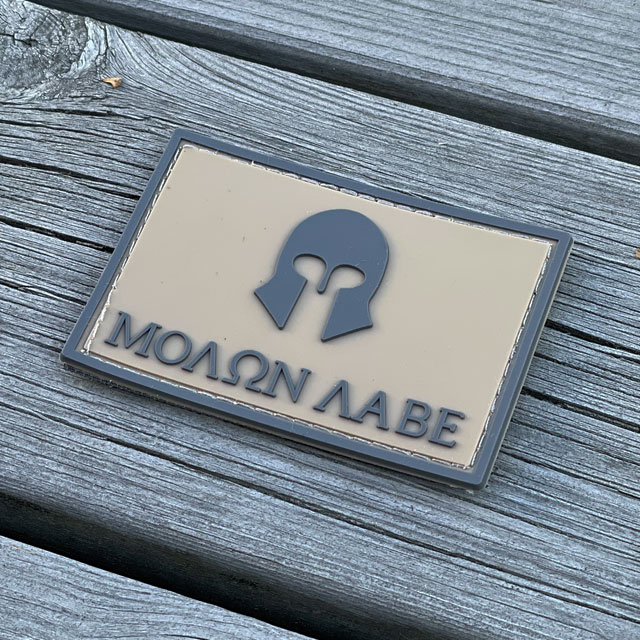 Molon Labe Coyote PVC Hook Patch with a wooden floor background from TAC-UP GEAR