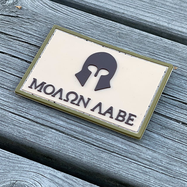 Molon Labe Multi Tan PVC Patch from TAC-UP GEAR with a wooded floor background