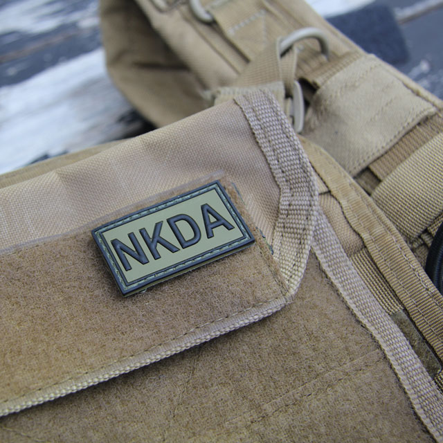 A NKDA Green/Black PVC Hook Patch mounted on a combat vest.