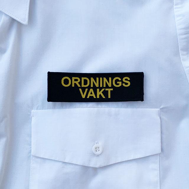 Ordningsvakt Avlångt Tygmärke på vit skjorta