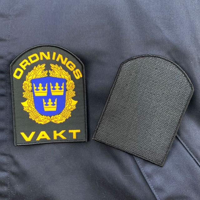 Ordningsvakt Rundad Kardborremärke mot blå jacka