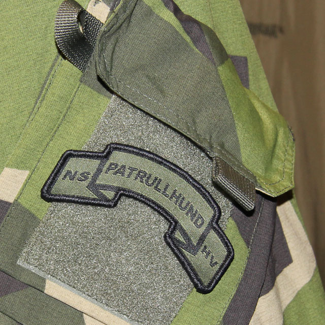 A mounted Patrullhund Hook Scroll Patch on a M90 camouflage NCWR Jacket.