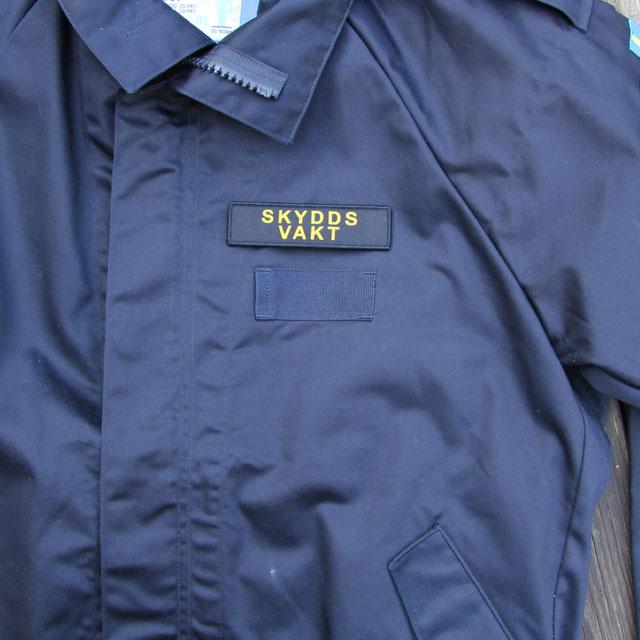 Marinens blåa uniformsjacka och ett Skyddsvakt Avlång Kardborremärke.