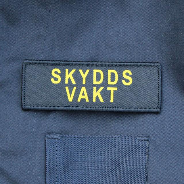 Skyddsvakt Avlång Kardborremärke på Marinens blåa uniformsjacka.