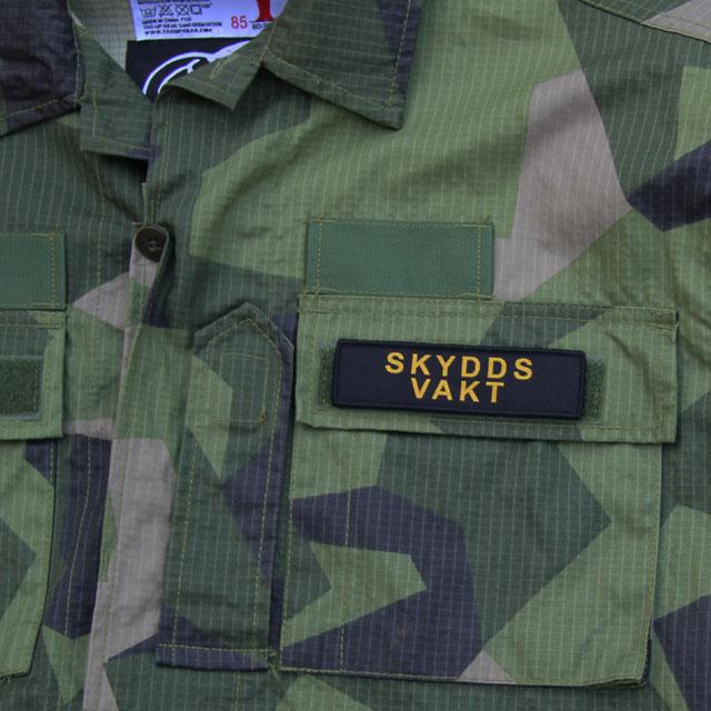 Ett Skyddsvakt Avlång Kardborremärke på en M90 uniform.