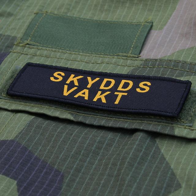 Skyddsvakt Avlång Kardborremärke med M90 kamouflage i bakgrunden.