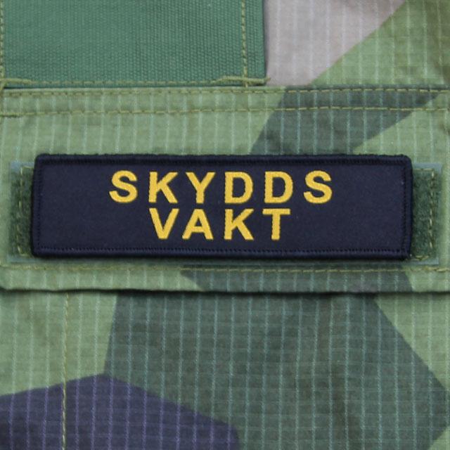 Ett Skyddsvakt Avlång Kardborremärke monterat på locket på en bröstficka på en M90 kamouflage jacka.