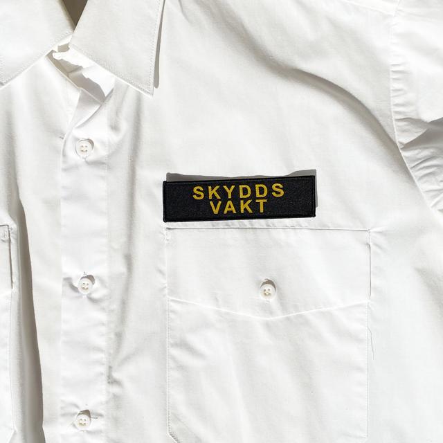 Skyddsvakt Avlångt Tygmärke på en vit skjorta direkt över vänster bröstficka