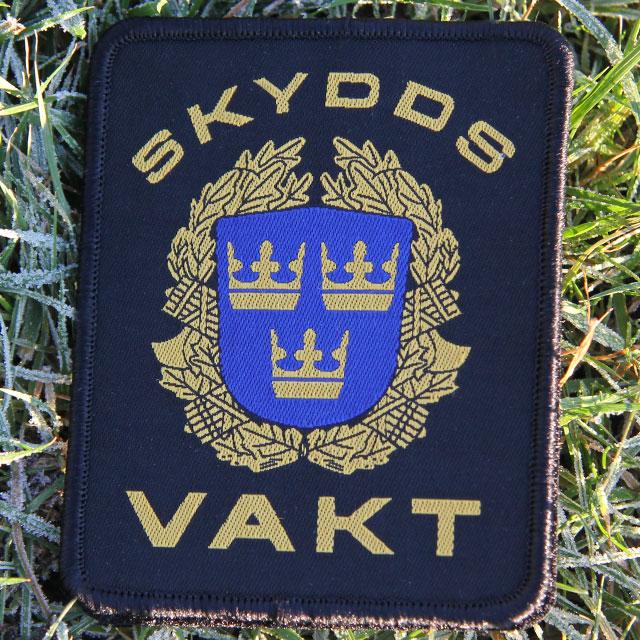 Det militära Skyddsvakt tygmärke kardborre Svart har text och mäke i fint gult och blått mot svart botten.