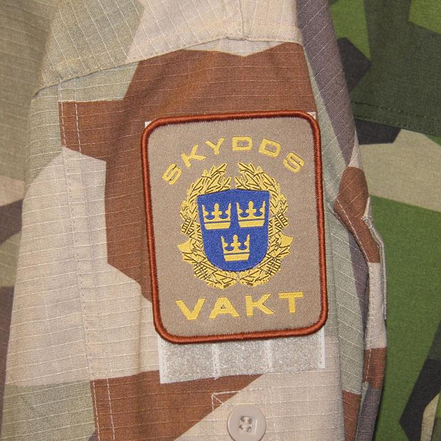 Ett Skyddsvakt Tygmärke Kardborre Öken monterad på M90K jacka.