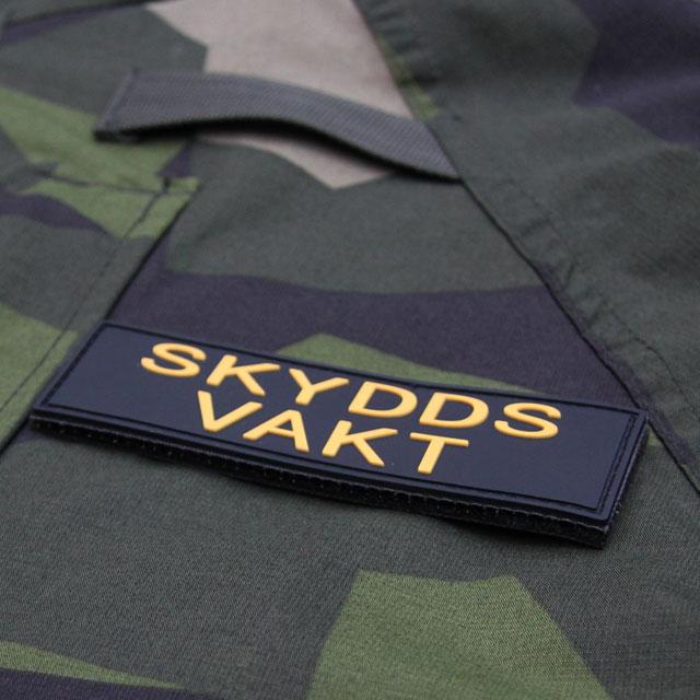 Produktfoto av ett Skyddsvakt PVC Avlång Kardborremärke mot en bakgrund av M90 kamouflage.