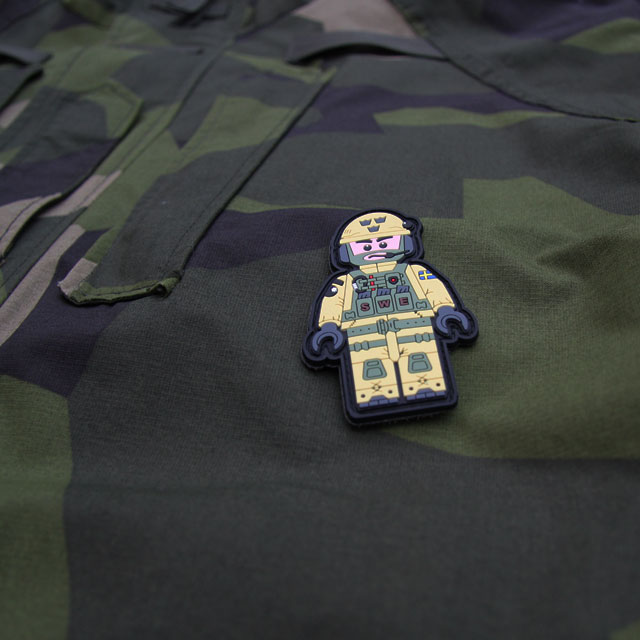 A SWE SOG PVC Figur Patch on M90 camouflage background.