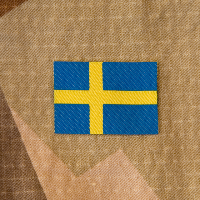 A Sweden Flag Arm Patch on M90K desert camouflage background.