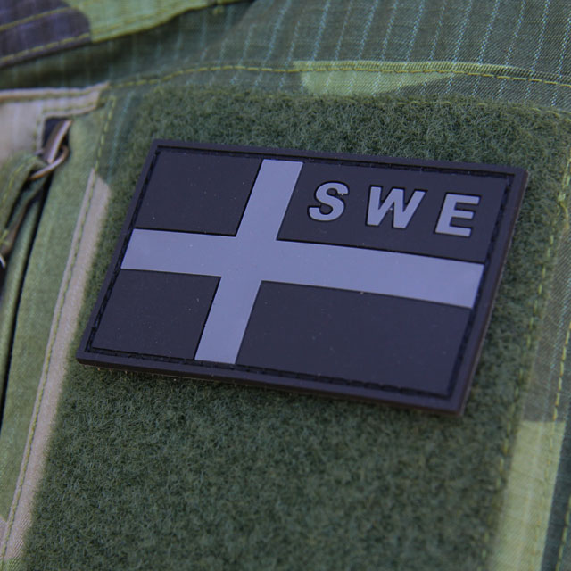 A mounted Sweden Flag OPS PVC Black/Grey Patch on the arm of a Field Shirt M90.