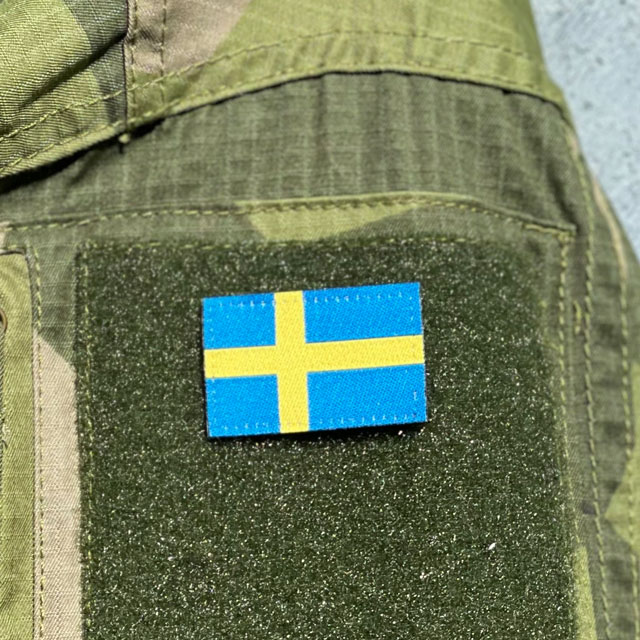 A Sweden Flag Hook Patch Arm mounted on the sleeve of a Fieldshirt M90