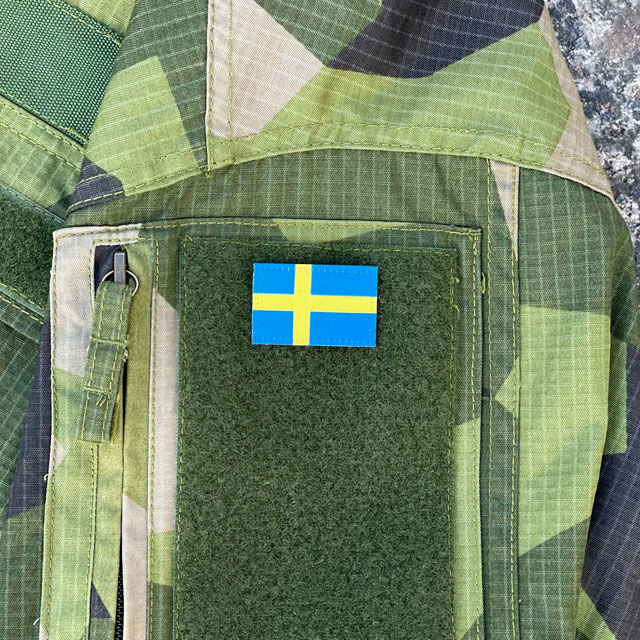 A Sweden Flag Hook Patch Arm seen mounted on a Fieldshirt in M90 camouflage