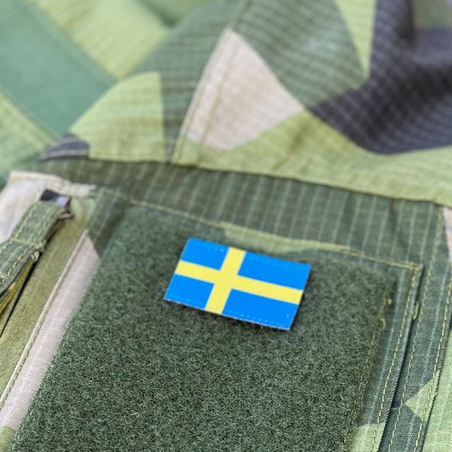Seen from an angle and mounted on loop fabric is a Sweden Flag Hook Patch Arm