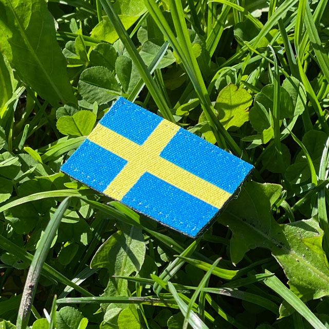 A Sweden Flag Hook Patch Arm with grass background