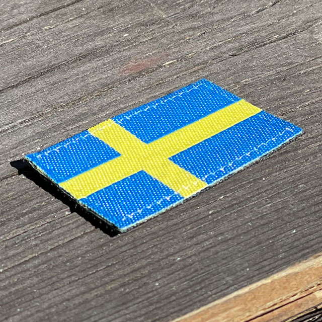 A Sweden Flag Hook Patch Arm on wooded floor background