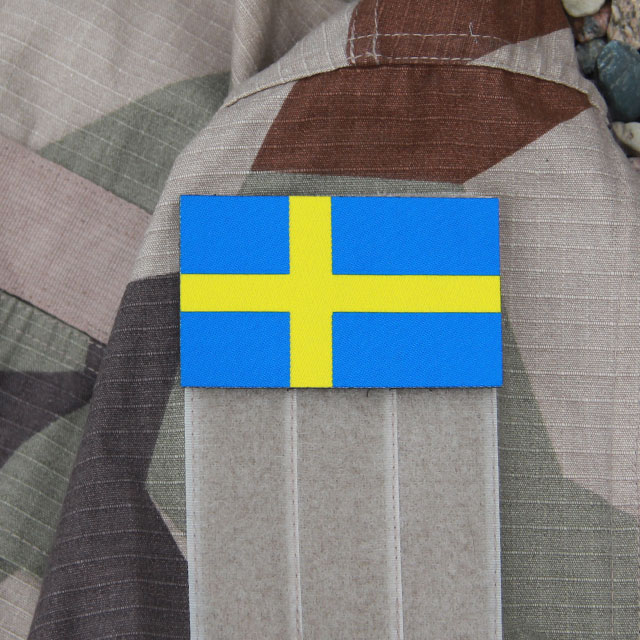 A Sweden Flag Large Hook Patch mounted on the arm of a M90K Desert jacket sleeve.