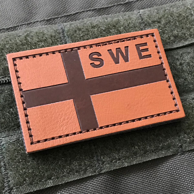 A Sweden Flag Leather Patch mounted on a ranger green plate carrier.