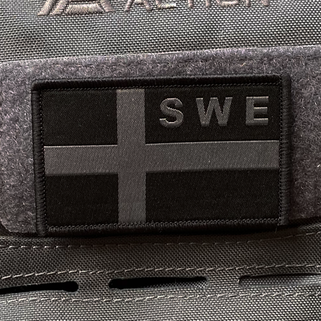 Sweden Flag OPS Nylon Black/Grey Patch mounted with velcro on a grey rucksack