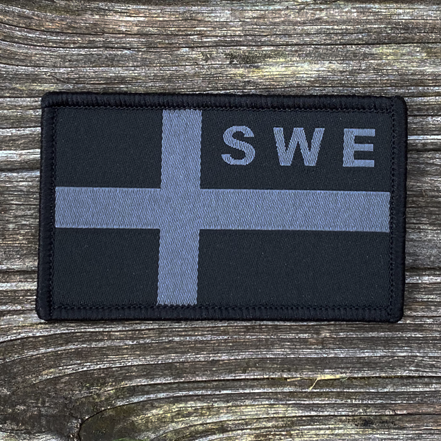 A Sweden Flag OPS Nylon Black/Grey Patch on wooded floor