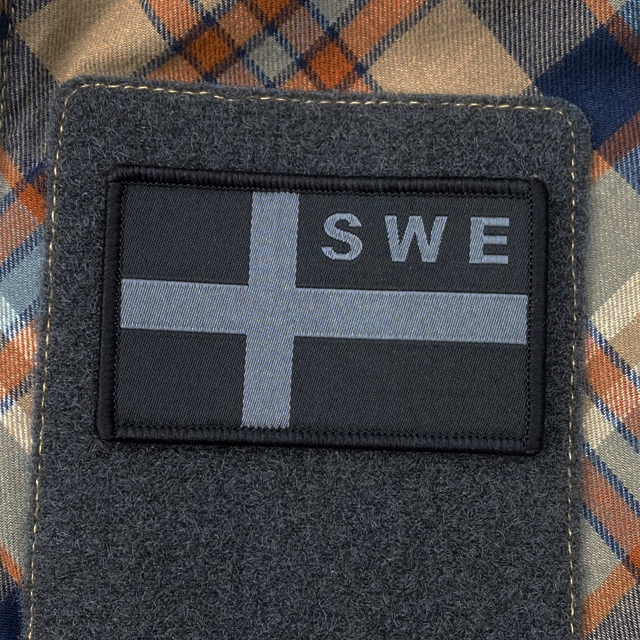 A Sweden Flag OPS Nylon Black/Grey Patch mounted with velcro on an plaid shirt